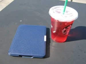 An e-reader and iced ta.